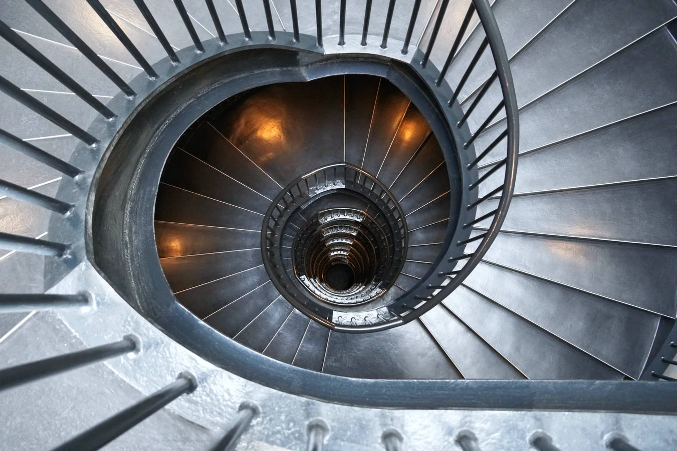 A seemingly endless spiral staircase as seen from above. Looking like an endless hole.